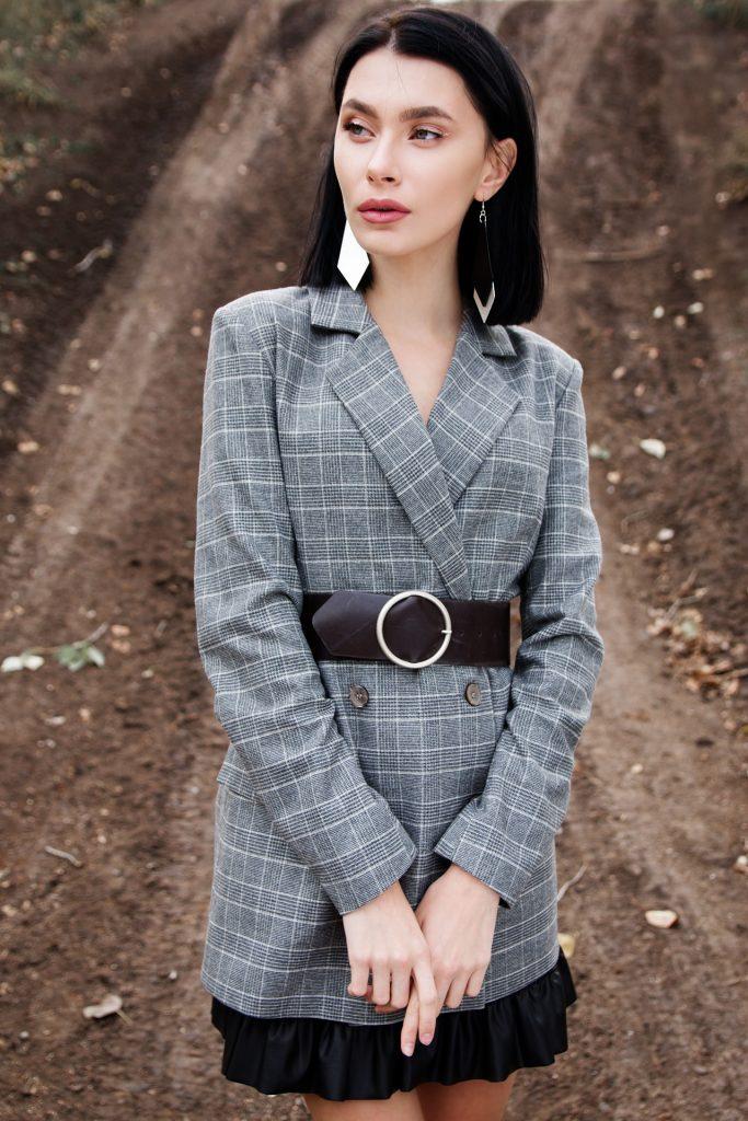 Mujer chaqueta gris cinturón negro