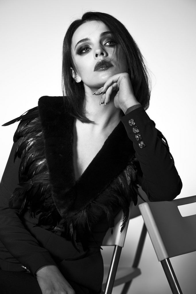 Mujer chaqueta negra con plumas